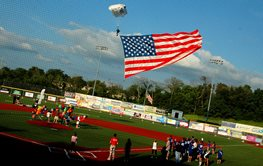 Parachuter with American flag landing on a baseball diamond