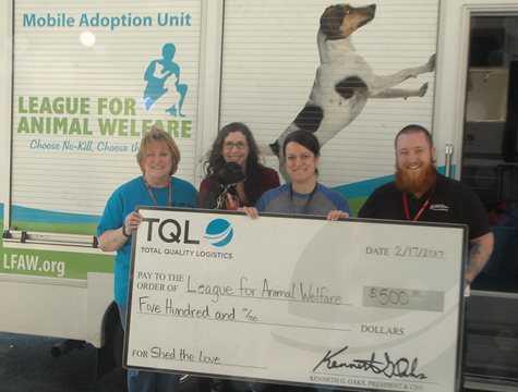 Four People Smile With a Giant TQL Check