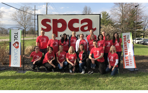 TQL Employees Posing In Front Of A SPCA Sign While Wearing Red