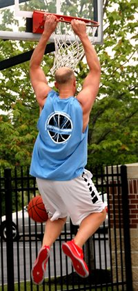 Man hanging on basketball rim after dunking