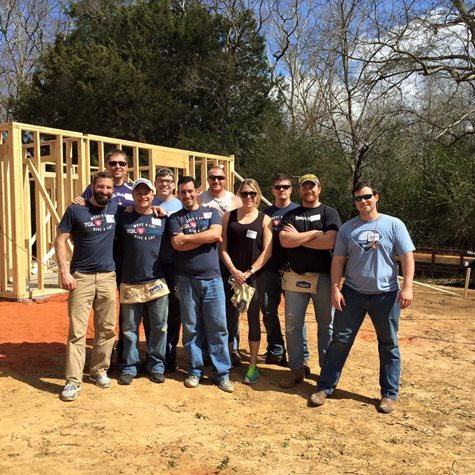 Employees with TQL Cares Shirts On Smile In Front Of The Wooden Foundation Of A House