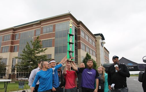 A Group Of People Raising A Trophy Together In Front Of The TQL Building