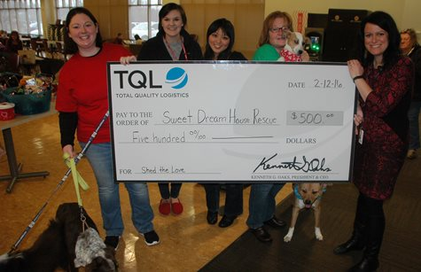 A Group Of Women And A Dog Smiling With A Giant TQL Check