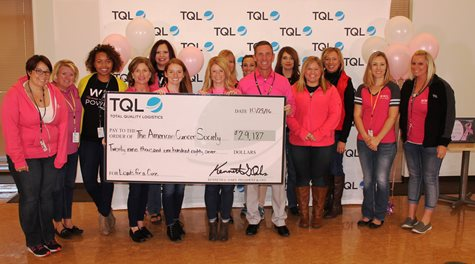 Employees In Pink Shirts Smiling With A Giant Check