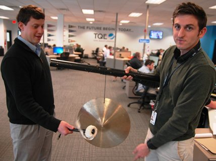 Two men holding and ringing a gong
