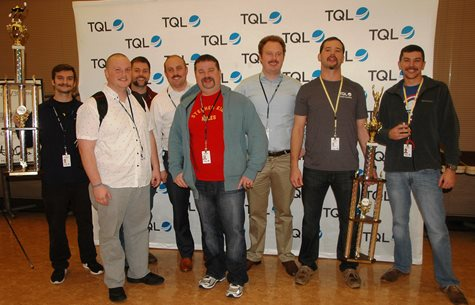 A Group Of Men Smiling With Trophies In Front Of A TQL Background