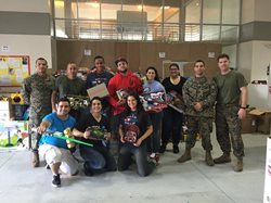 People and army men holding gifts posing for a picture