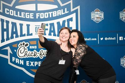 Two women taking selfie in front of College football hall of fame backdrop