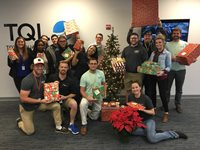 TQL Employees Smiling With Christmas Gifts for CASA