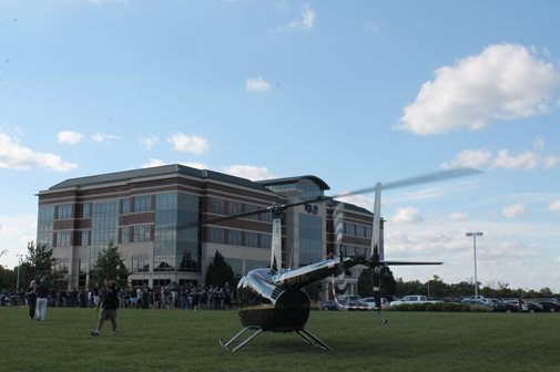 A Helicopter Landind On The Grass Outside The TQL Building