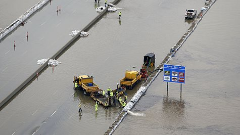 A Highway Flooded With A Couple Trucks And A Sign Sticking Out Of The Water