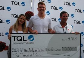 Andy Dalton and TQL employees holding check in front of TQL backdrop