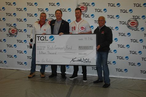 Three Employees And A Reds Player Smiling In Front Of A TQL Background With A Giant Check