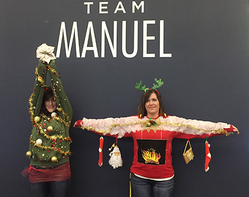 Two Women Dressed As Christmas Items In Front Of A Grey Team Manuel Wall
