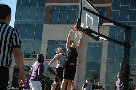 One Man Dunking While The Other Playing Defense On The Basketball Court OUtside Of TQL