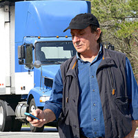 Truck driver using TQL Carrier Dashboard on his mobile device.